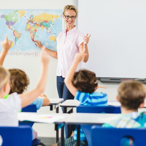 Teacher looking at student raised hands in a class room