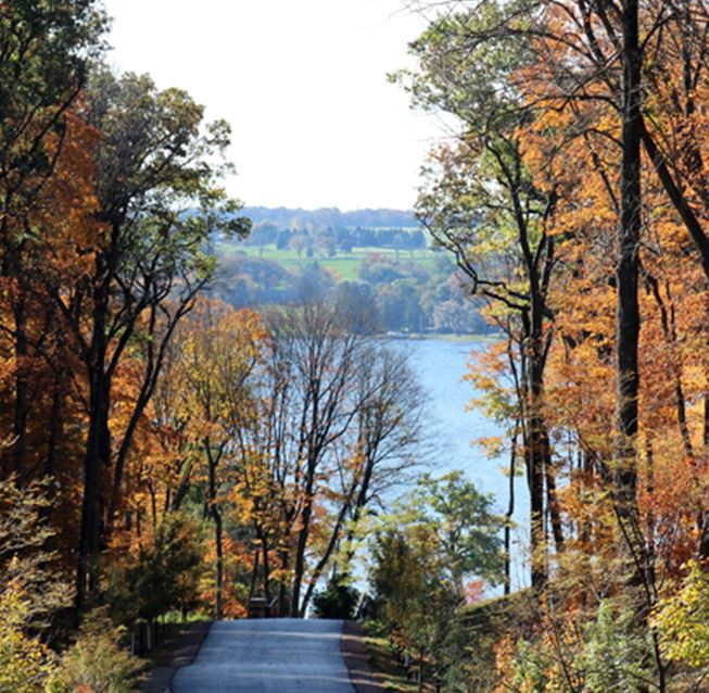 Rural country road with bright fall foliage in Wisconsin with Lake Geneva in the background